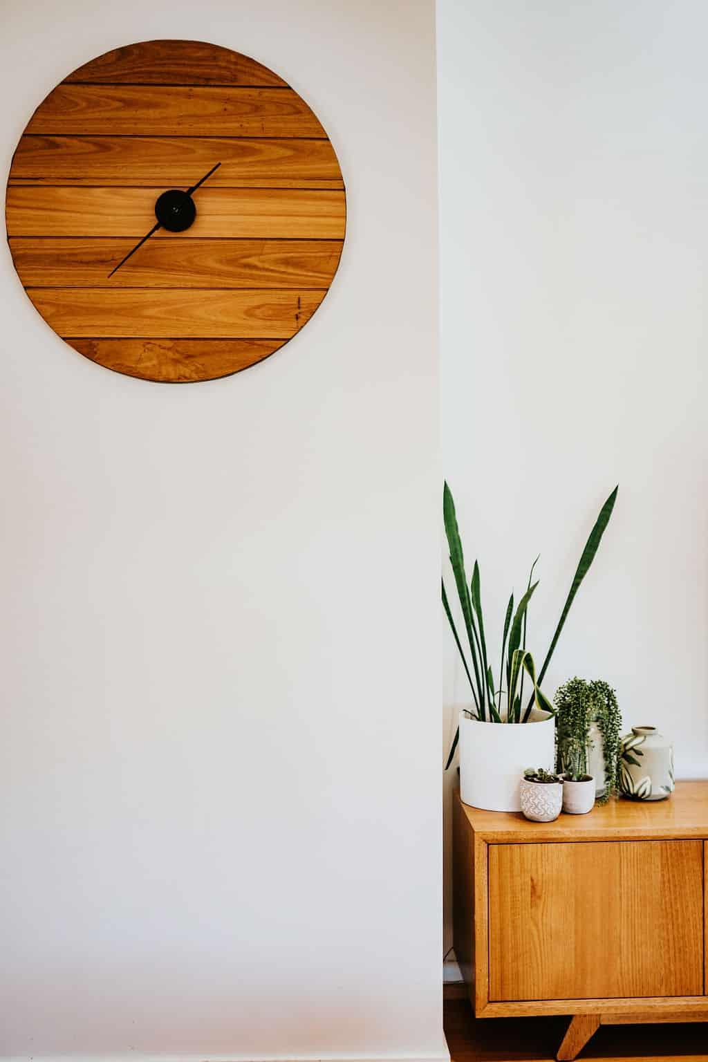 Locspec Building Oak Flats Renovation - wooden clock on a white wall.